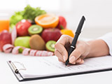 Doctor writing prescription for patient, making diet plan at workplace with fresh fruits, panorama