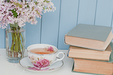 Gentle bunch of lilac, vintage books and china teacup on the table on blue wooden background