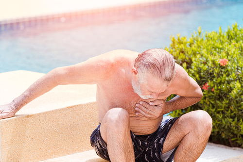 Elder pain suffer from heart attack at swimming pool in summer hot sunny day